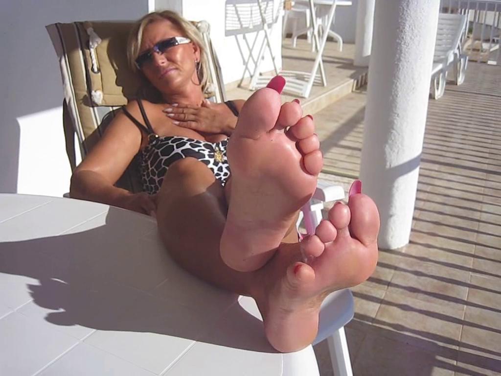 Une blonde mature exhibe ses pieds au bord de la piscine.