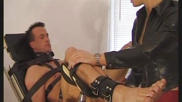Une maîtresse blonde joue avec le cul d'un soumis attaché