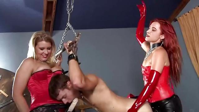 Séance de gode-ceinture avec dominatrices en rouge et noir